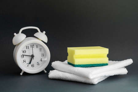 White round alarm clock, yellow foam sponge for washing dishes and two white household rags for cleaning on a dark background. Concept of world cleanliness day. Close-up, copyspace.