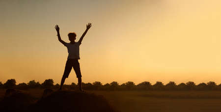 Silhouette of a happy jumping child-boy, over a haystack on the background of a field with a beautiful sunset.The concept of a carefree childhood. Beautiful summer landscape, copyspace, banner