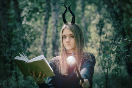 A young girl with long hair in a witch costume, with a staff in her hands, conjures a book. Halloween, selective focus, smoke in the woods. Tinting for an old photo with a grainy overlay