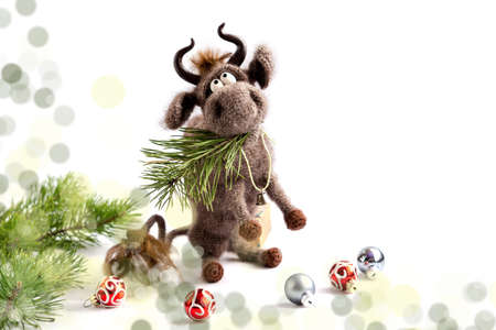 A knitted brown toy bull sits on its hind legs with a pine branch in its mouth.