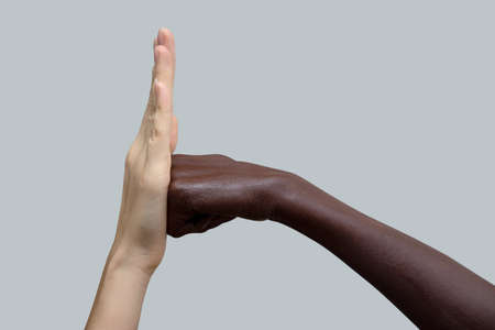Two hands, black and white. A black fist strikes a white palm.The concept of inter-racial friendship and respect, the fight against racism. Close-up, selective focus.