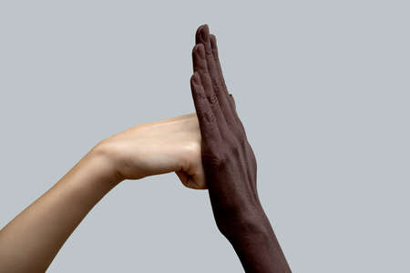 Two hands, black and white. A white fist hits a black palm.The concept of inter-racial friendship and respect, the fight against racism. Close-up, selective focus.