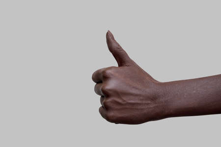 The sign of the thumb. A hand with black skin showing the like sign on a gray isolated background. Close-up, selective focus. 版權商用圖片