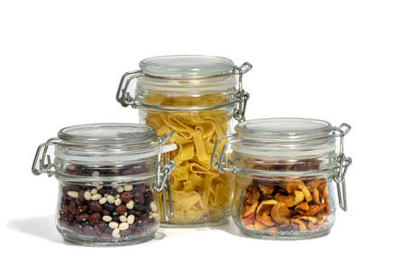 Assortment of raw grains, cereals and pasta in glass jars on a white isolated background. The concept of zero waste. Close-up, selective focus. 免版税图像