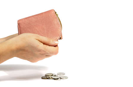 Women's hands shake money out of an empty pink wallet. White isolated background, close-up, selective focus, copy space. Concept of financial expenses and income.