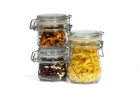 Assortment of raw grains, cereals and pasta in three glass jars on a white isolated background. The concept of zero waste. Close-up, selective focus.