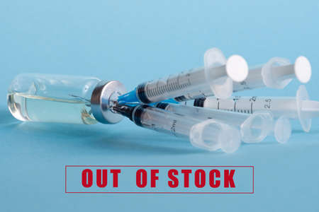 An ampoule with medicine and five syringes stuck in the bottle cap, on the background of the inscription: out of stock. The concept of a shortage of influenza virus vaccines.