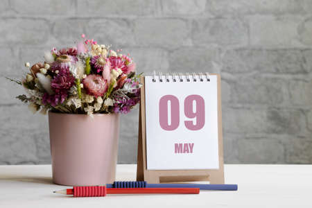 may 09.09-th day of the month, calendar date.A delicate bouquet of flowers in a pink vase, two pencils and a calendar with a date for the day on a wooden surface ..