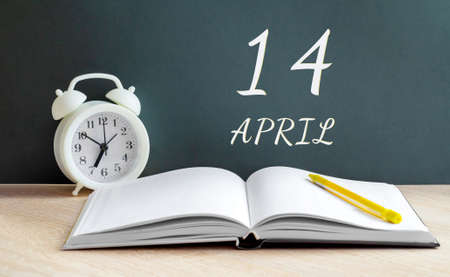 April 14.14-th day of the month, calendar date.A white alarm clock, an open notebook with blank pages, and a yellow pencil lie on the table. Spring month, day of the year concept.