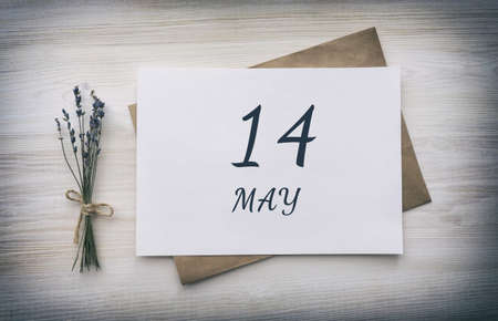 may 14.14th day of the month, calendar date. White blank of paper with a brown envelope, dry bouquet of lavender flowers on a wooden background. Spring month, day of the year concept.