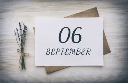 september 06.06th day of the month, calendar date.White blank of paper with a brown envelope, dry bouquet of lavender flowers on a wooden background. Autumn month, day of the year concept.