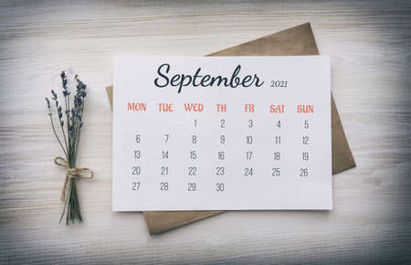 Page from the calendar for the full month: September 2021. Numbers, days of the week, name on white paper, on top of kraft paper envelope, next to bouquet of dried lavender on wooden white background.