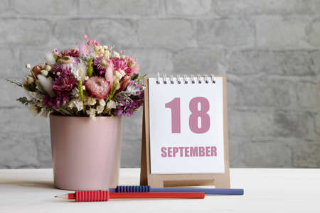 september 18. 18-th day of the month, calendar date.A delicate bouquet of flowers in a pink vase, two pencils and a calendar with a date for the day on a wooden surface ..