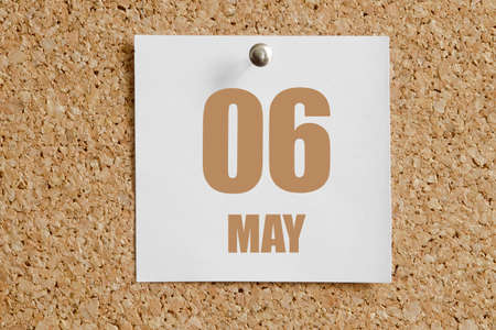 may 06.06th day of the month, calendar date. White calendar sheet attached to brown cork board. Spring month, day of the year concept.