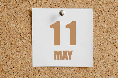 may 11.11th day of the month, calendar date. White calendar sheet attached to brown cork board. Spring month, day of the year concept.