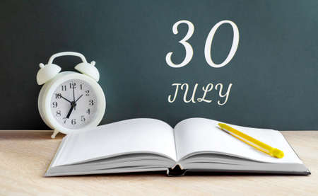 july 30.30-th day of the month, calendar date.A white alarm clock, an open notebook with blank pages, and a yellow pencil lie on the table. Summer month, day of the year concept. Stock fotó
