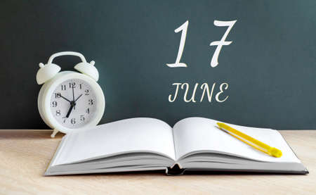 june 17.17-th day of the month, calendar date.A white alarm clock, an open notebook with blank pages, and a yellow pencil lie on the table. Summer month, day of the year concept.