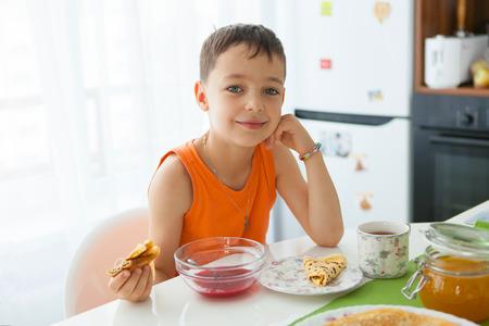 niños desayunando: Niño pequeño desayunando en la cocina
