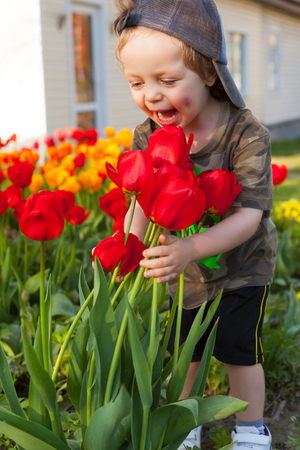 Happy child against spring flowers background. Stock Photo