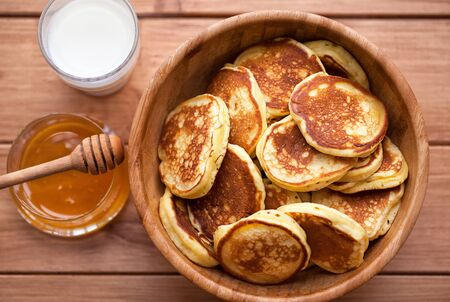 Homemade Pancakes with honey and glass of milk in wooden dish.