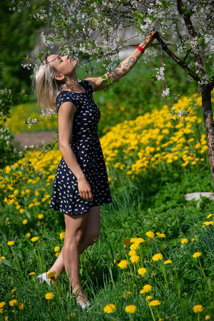 A portrait of a beautiful young girl in a blue dress in the garden with apple trees blosoming having fun and enjoying smell of flowering spring garden Stockfoto
