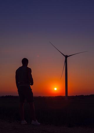 Man looking windmills at sunset.