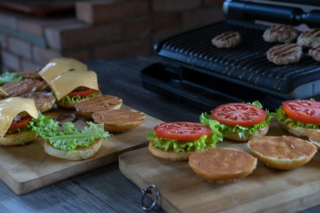 Cheeseburgers and hamburgers being grilled