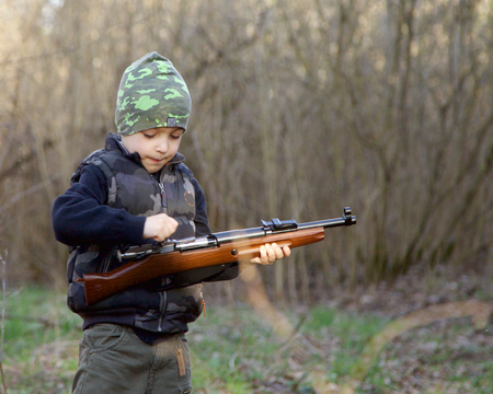 Cute child in soldier uniform playing toy gun outdoors.