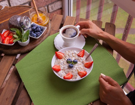 Fitness woman have a healthy breakfast. Healthy Homemade Oatmeal with Berries