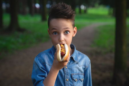 a young boy takes a bite of a hot dog 写真素材