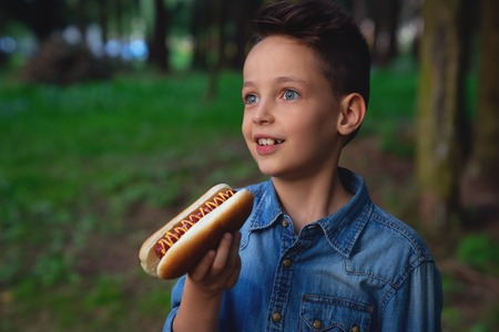 a young boy takes a bite of a hot dog Stock fotó
