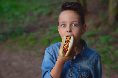 a young boy takes a bite of a hot dog 스톡 콘텐츠