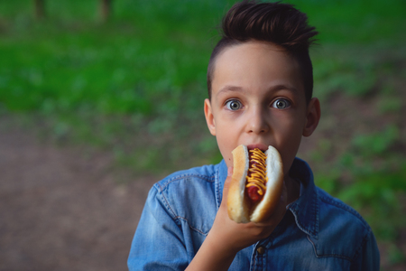 a young boy takes a bite of a hot dog Banque d'images