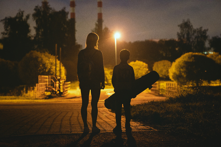 Woman with son riding on longboard in park at night time 版權商用圖片