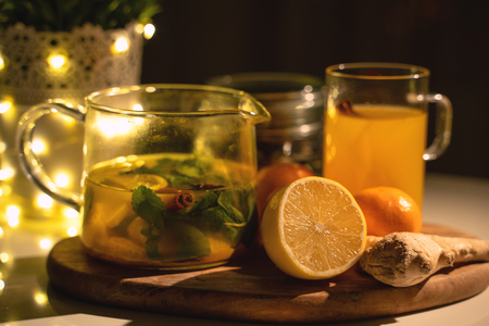 Spicy tea in a cup with cinnamon, honey, turmeric on a wooden background. Hot drink. Copy space. Christmas lights