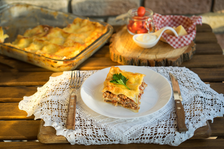 Classic hommade Lasagna with bolognese sauce on wooden table with lace tablecloth Imagens