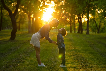 Mother and little son in park or forest, outdoors. Hugging and having fun together Imagens