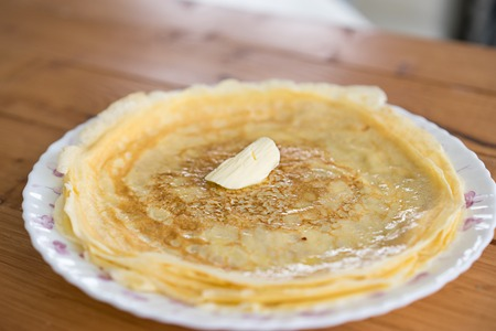 Fried pancakes with a piece butter on wooden table