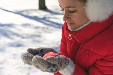 Hands in Knitted Mittens holding Steaming Cup of Hot Tea on Snowy Winter Morning Outdoors. Woman holds Cozy Festive Red Mug with a Warm Drink on Christmas Morning