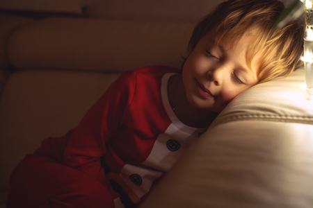 Beautiful boy sleeps on the sofa in Christmas night. Child sleeping under a Christmas tree