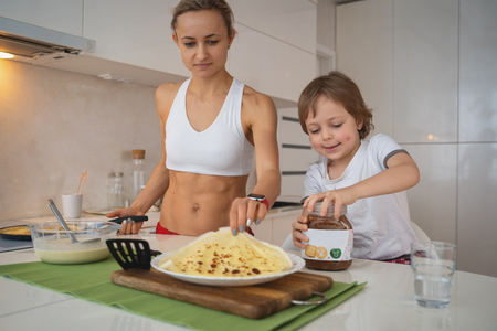 Young sporty woman with child cooking pancakes at kitchen
