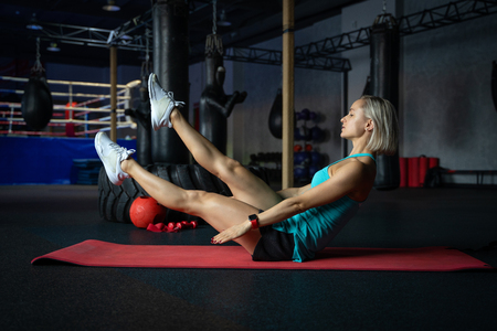 Young attractive cool woman practicing abs exercise, Sit Ups, working out, wearing sportswear, full length silhouette in boxing gym.