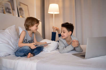 Two children, boys in parents bed at morning with laptop and tablet. Brothers play computer games. Siblings and gadgets.