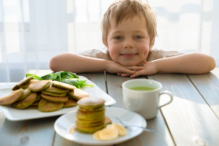 Cute five year boy with stack of spinach pancakes Imagens