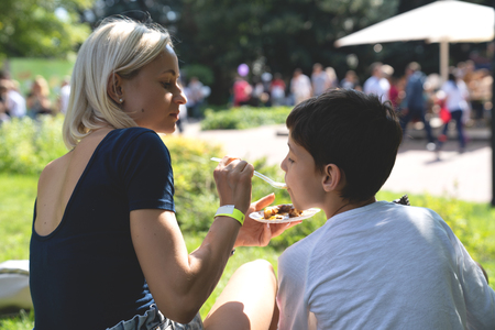 Portrait of mother and son eating street food in the park.