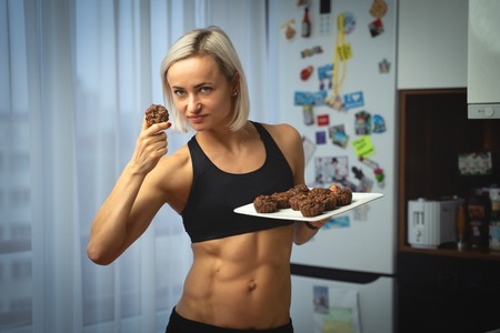 Young caucasian woman with abdominal muscle with healthy muffins. Healthy nutrition concept
