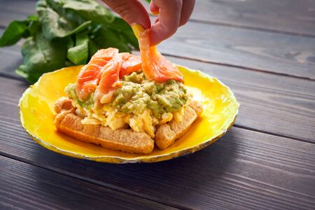 Belgian waffle with scrambled egg, avocado and salmon on wood table. Plate, bacon. Keto Breakfast variation