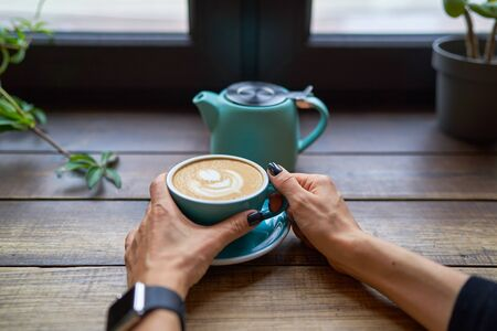 A cup of delicious strong coffee in female hands. Concept drinks, lifestyle, work, background