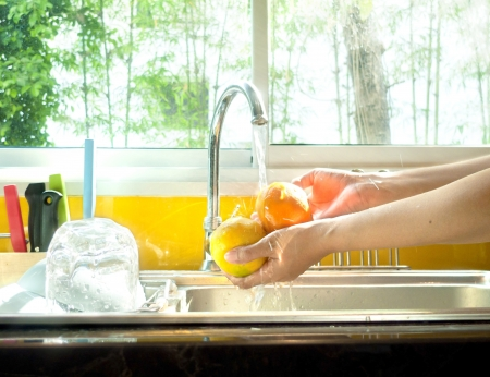 Image of woman washing fresh orange.