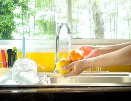 Image of woman washing fresh orange.